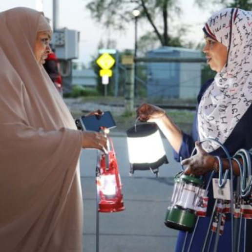 Two women in hijabs talking and holding camping lamps.