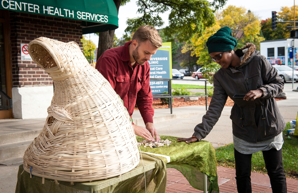 A woman and a man stand at a table with a green tablecloth, a variety of shells, and a woven basket sculpture.