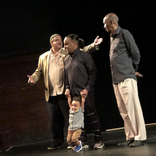 Three men on stage, one man stands with a swinging toddler.