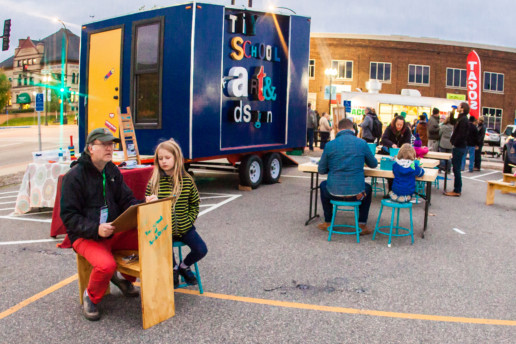 People sit at outdoor tables with art supplies in front of a blue trailer that says Tiny School of Arts & Design