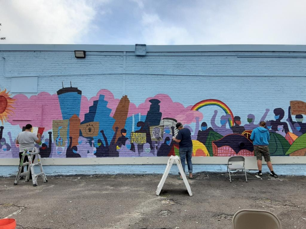 Painters working on a mural featuring a cityscape, protestors, and a rainbow,