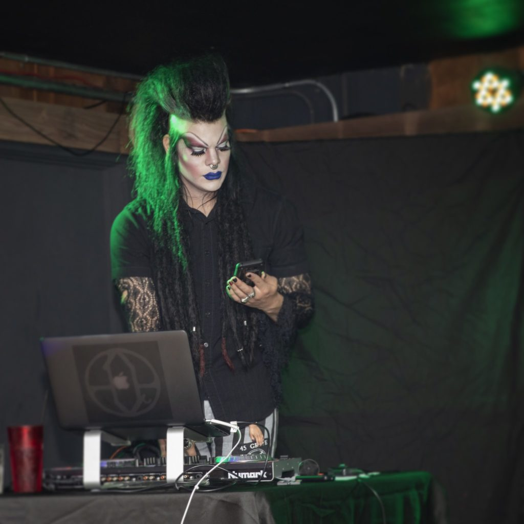 A person with tall, long black hair and makeup, dressed in black, stands at a computer DJing