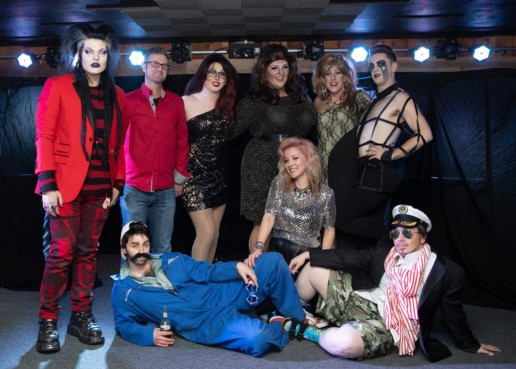 A group of people in spooky and glamorous costumes.