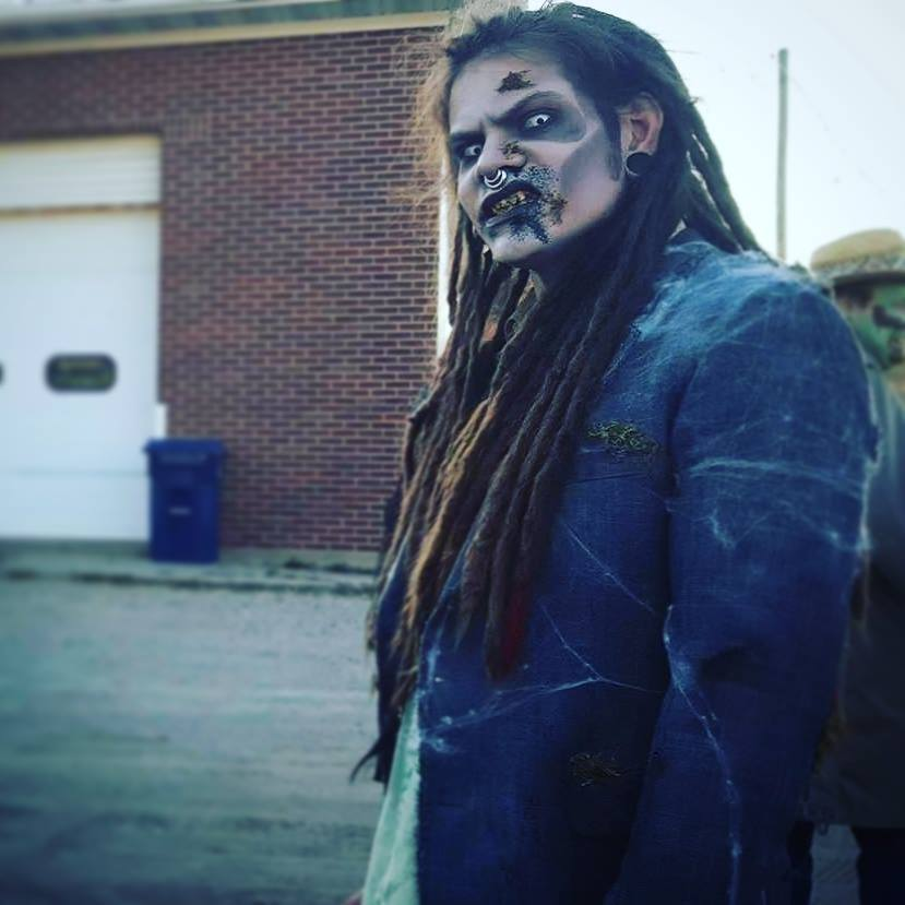 A person in zombie makeup growls at the camera