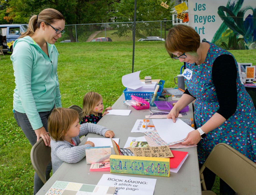 A woman in a teal sweater stands at a tabl with two children, working on book-making creative activities with Jes Reyes, in a blue floral dress.