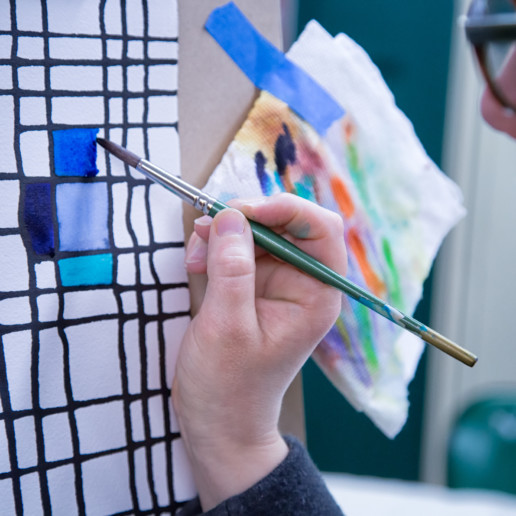 Jes Reyes, a woman with short brown hair, paints a colorful grid
