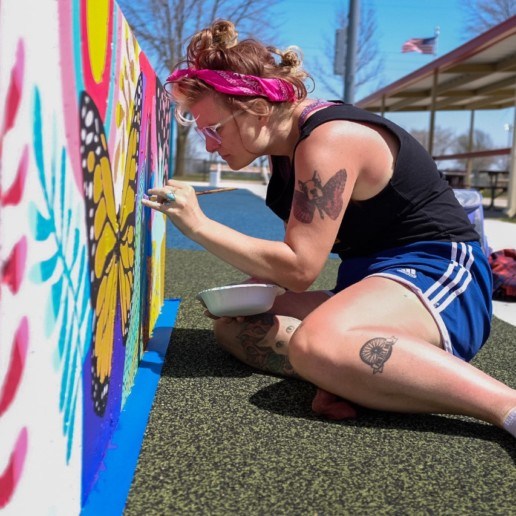 A woman in a tank top and shorts paints a bright mural with a butterfly